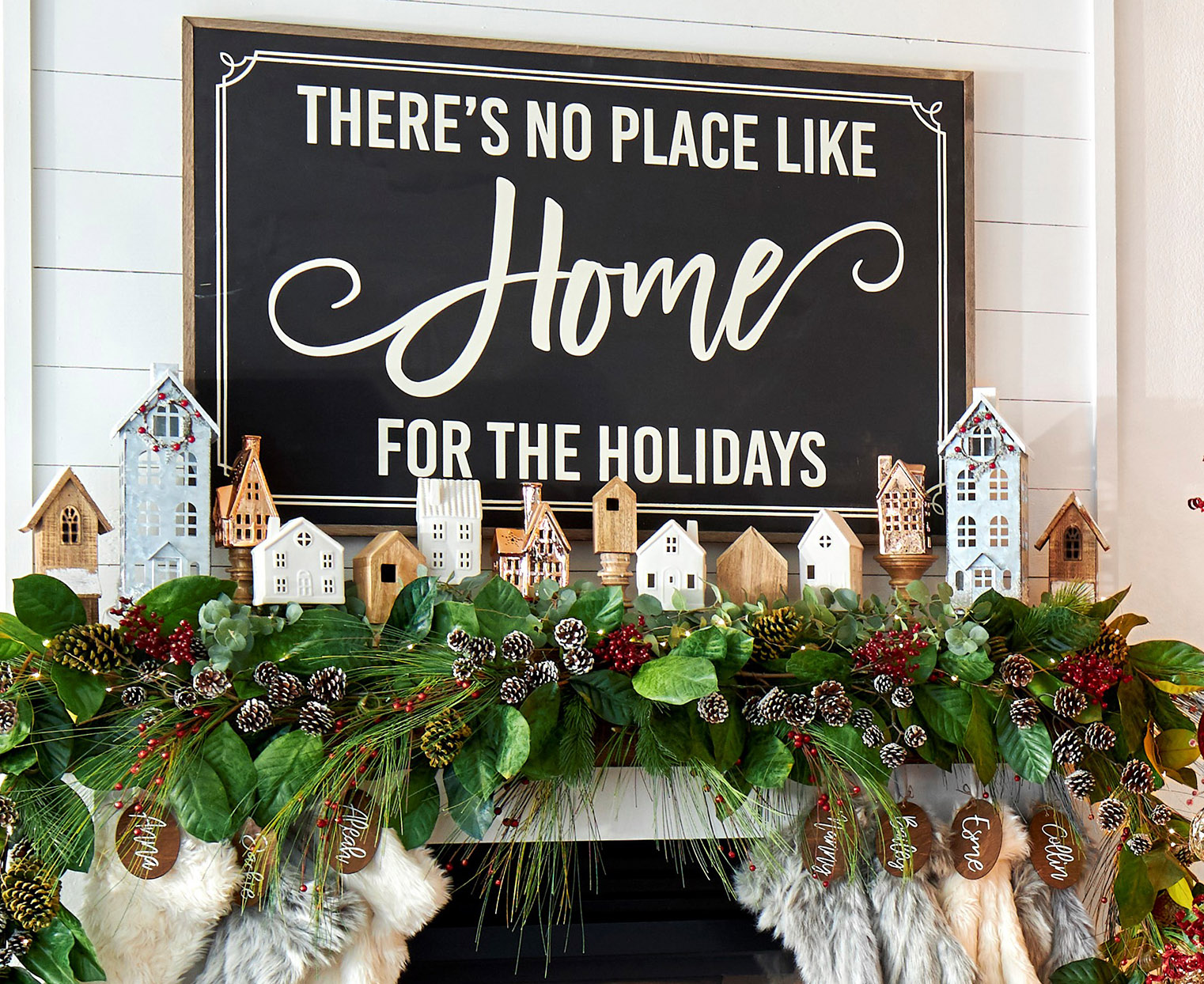 white mantel with green garland and wood christmas village