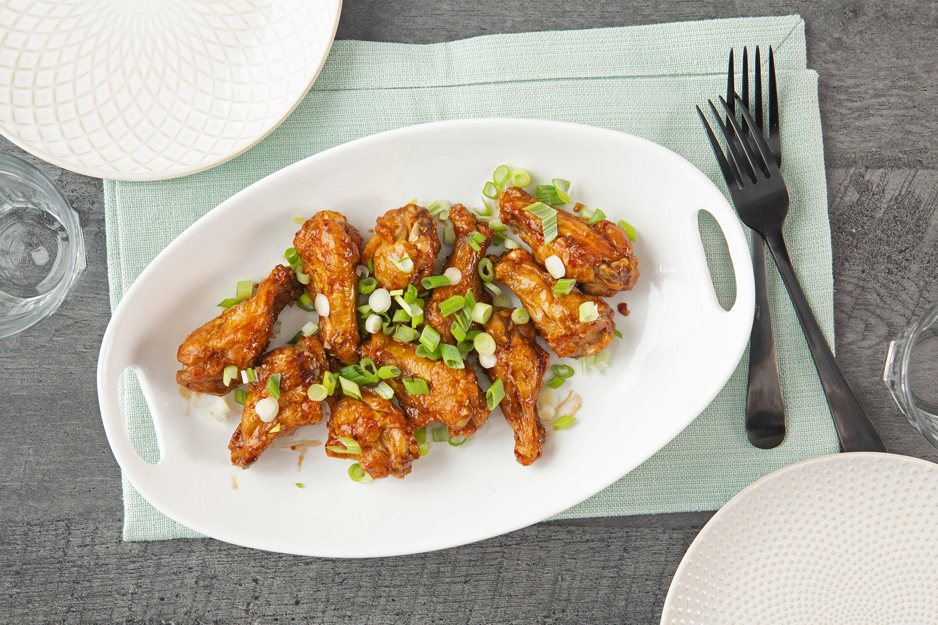 plate of chicken wings topped with green onions