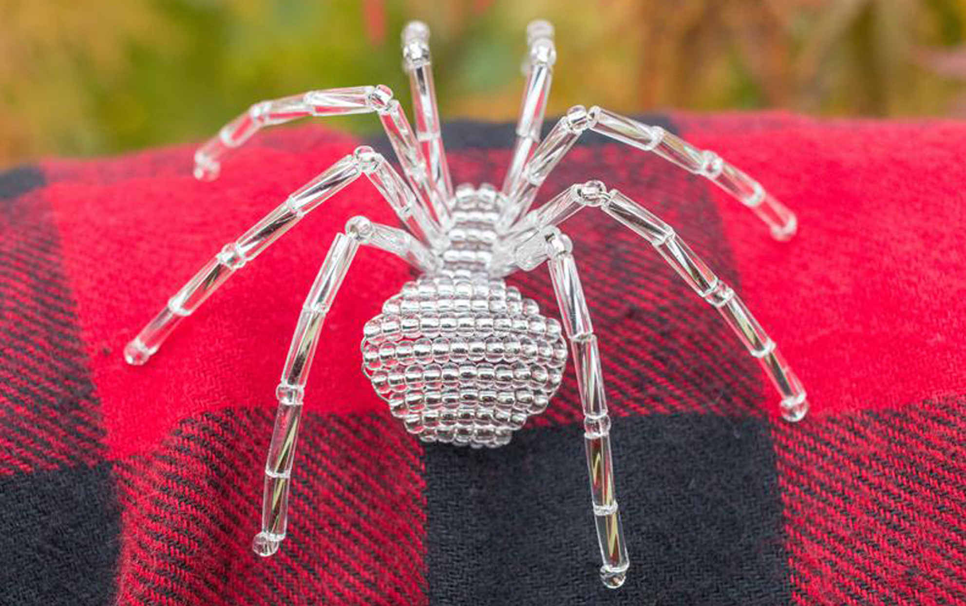 Glass spider Christmas ornament on a red and black checkered blanket