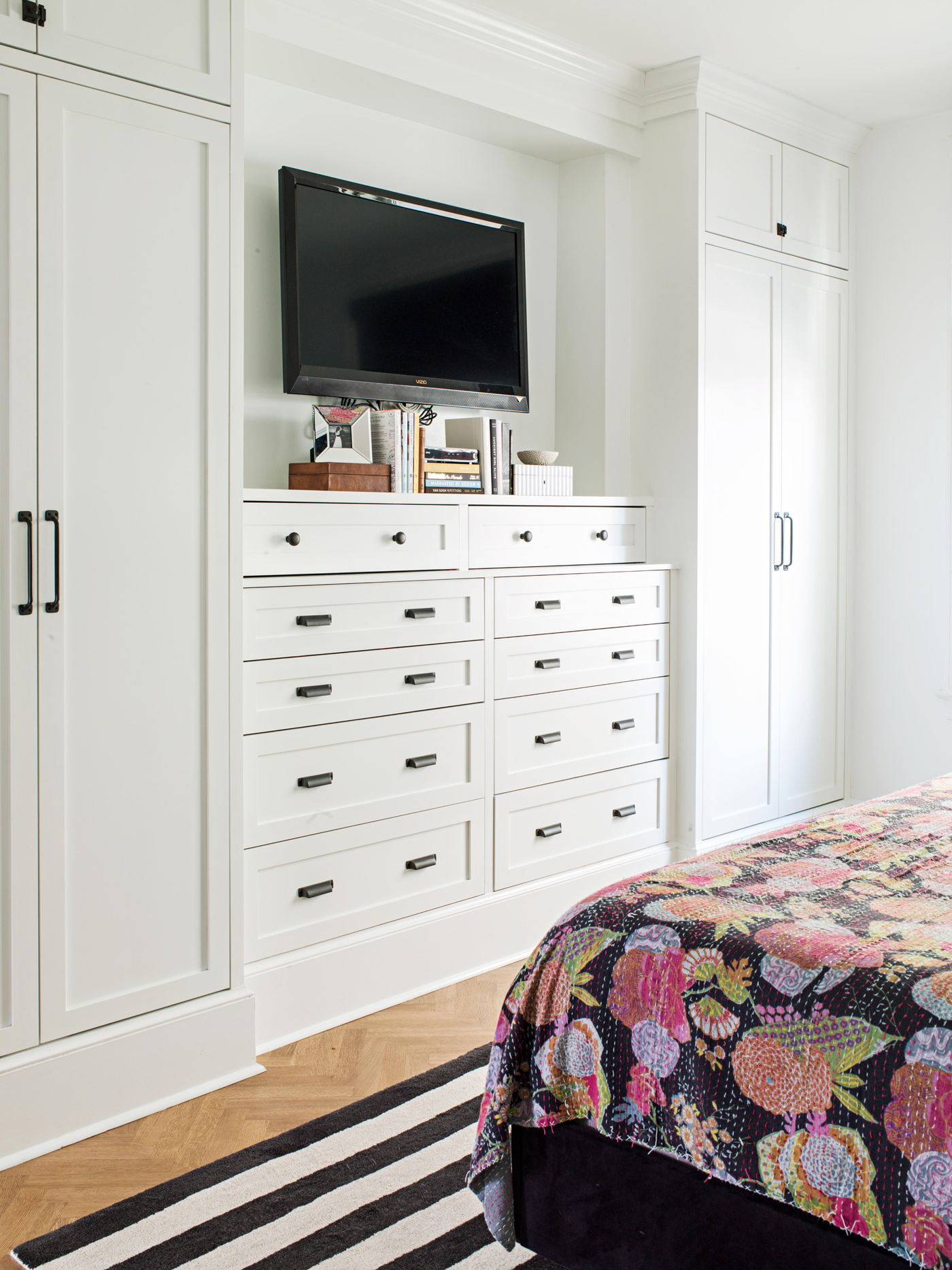 white built-in drawers and cabinets with tv
