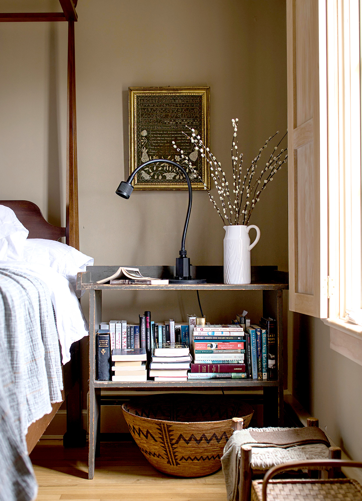 Corner of bedroom with nightstand shelf with books