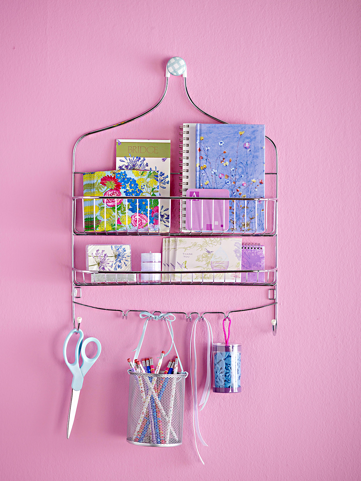 Hanging shelf with supplies on pink wall
