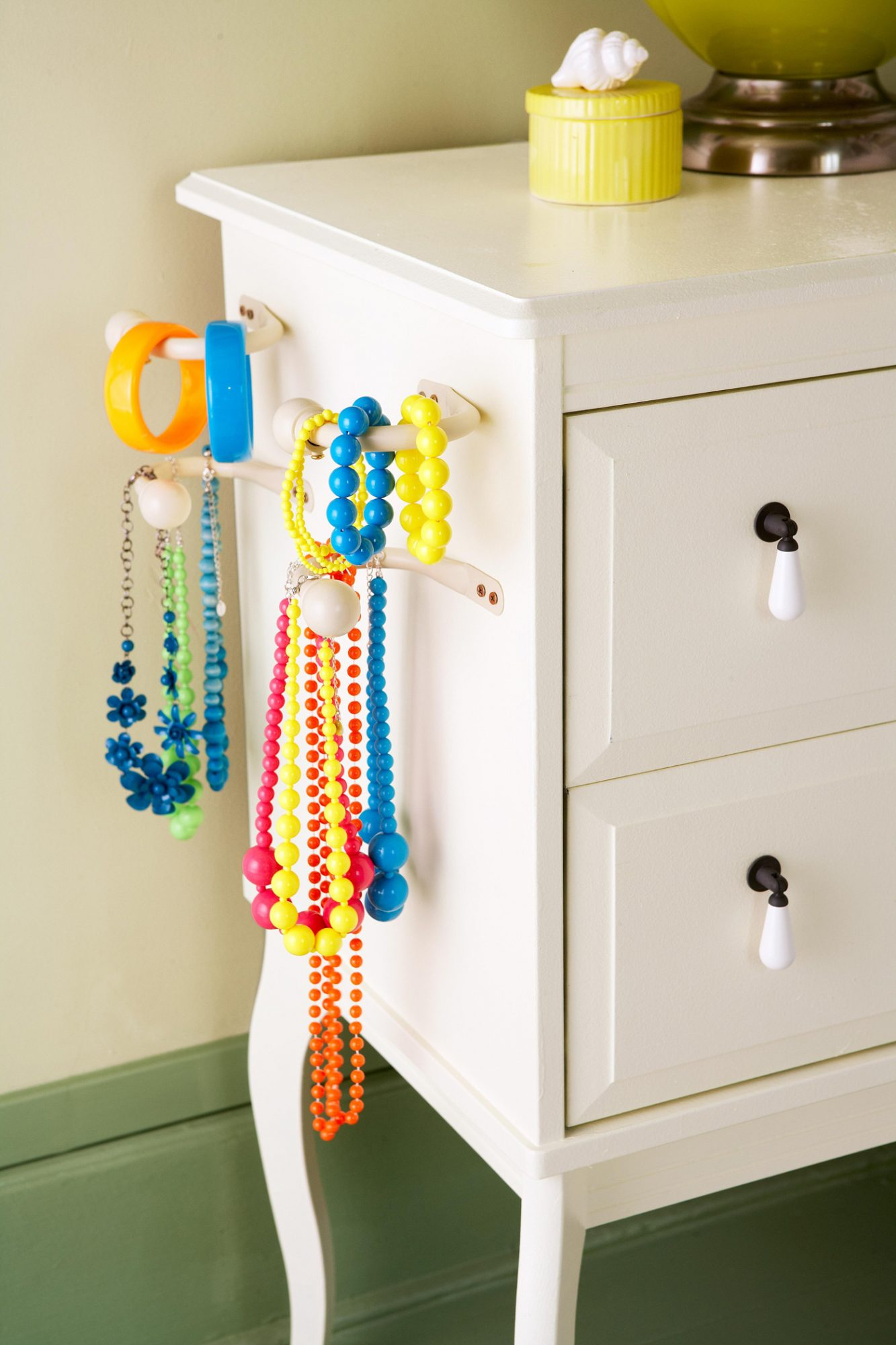 necklaces on large white hooks mounted on dresser side