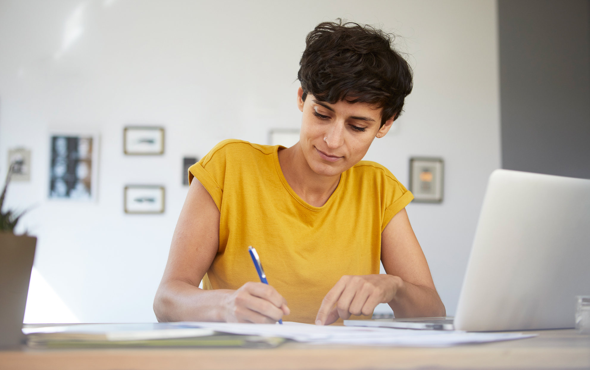 Woman with short hair writing near a laptop