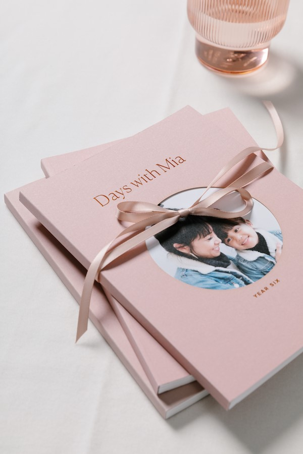 stack of pink books with circle shaped photos on the front