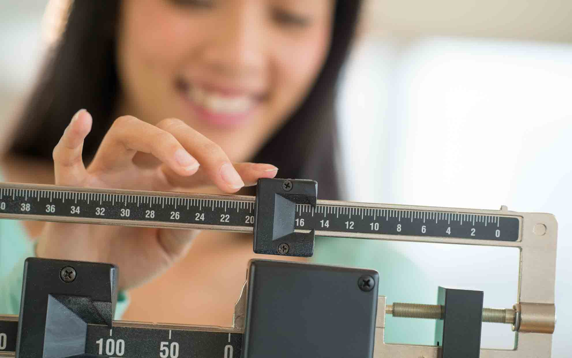 woman weighing herself on a slide scale