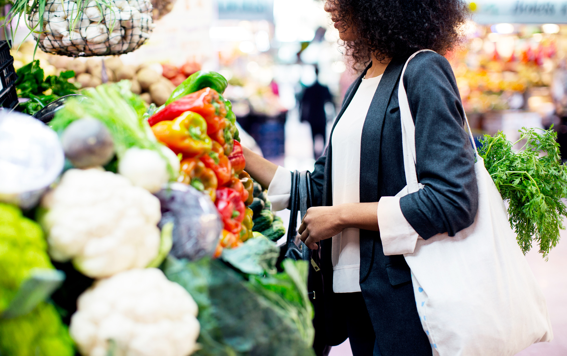 Woman shopping in a grocery store for fresh produce