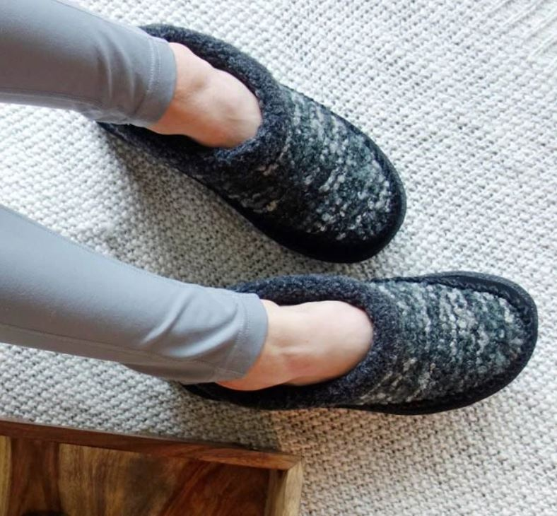 two feet wearing black and gray wool slippers