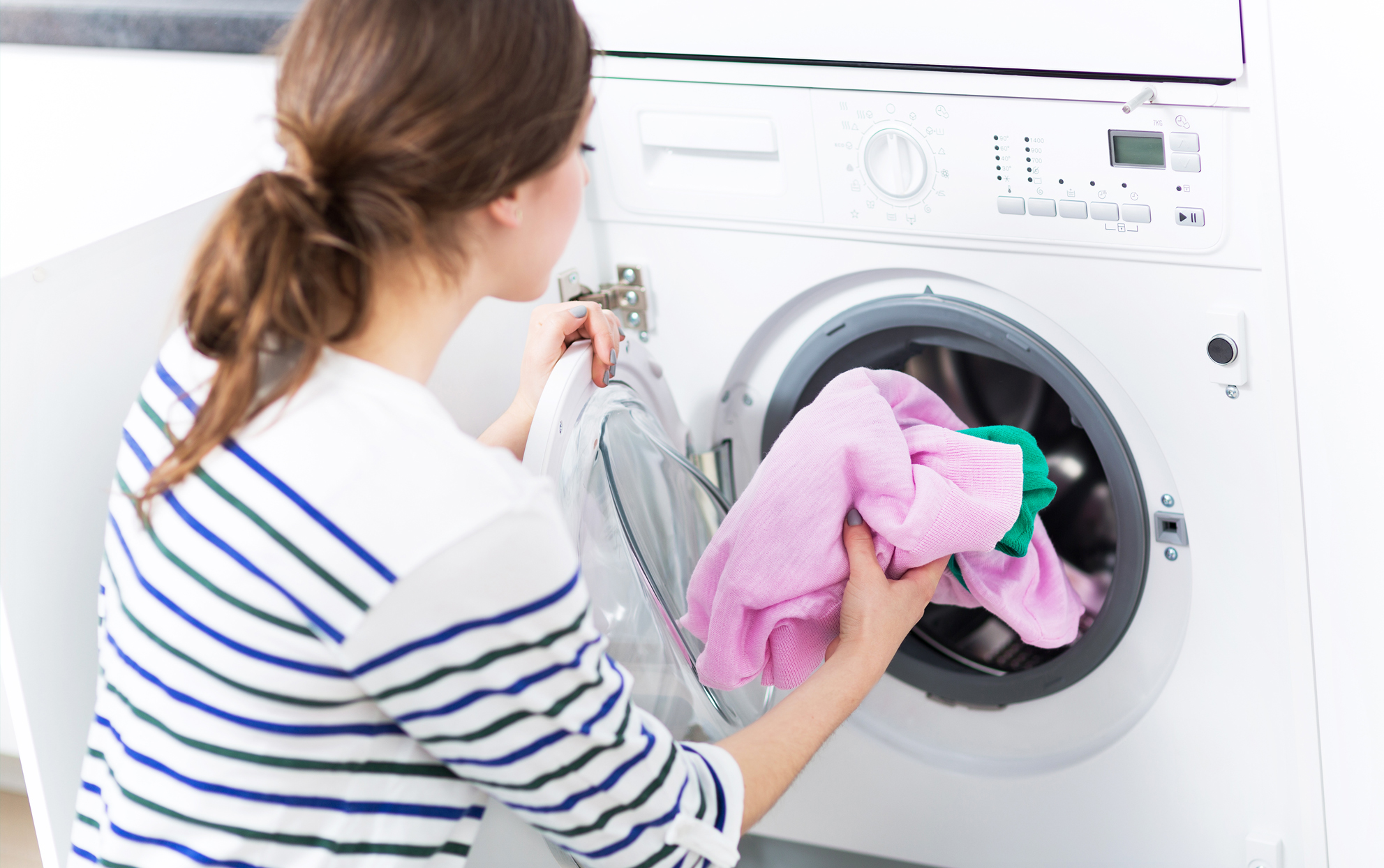 woman putting laundry into the washing machine