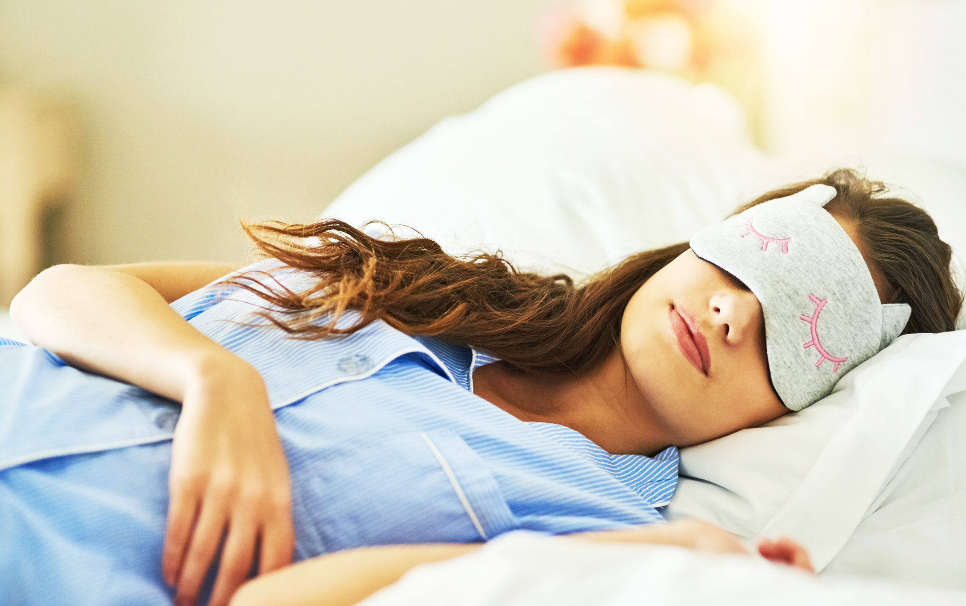 woman sleeping in bed with an eye mask