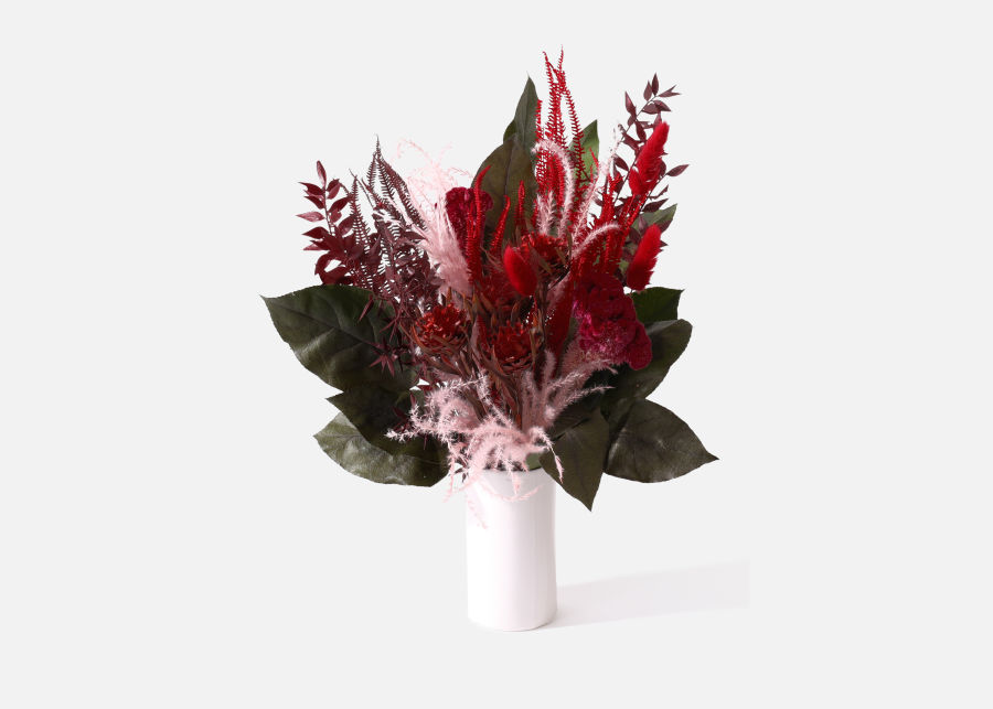 dried burgundy flowers and green leaves in a white vase