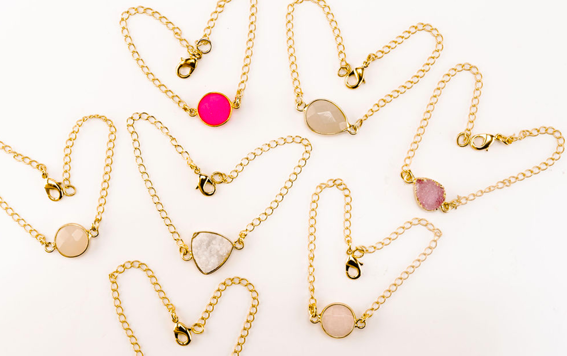 multiple gold and stone bracelets on a light background
