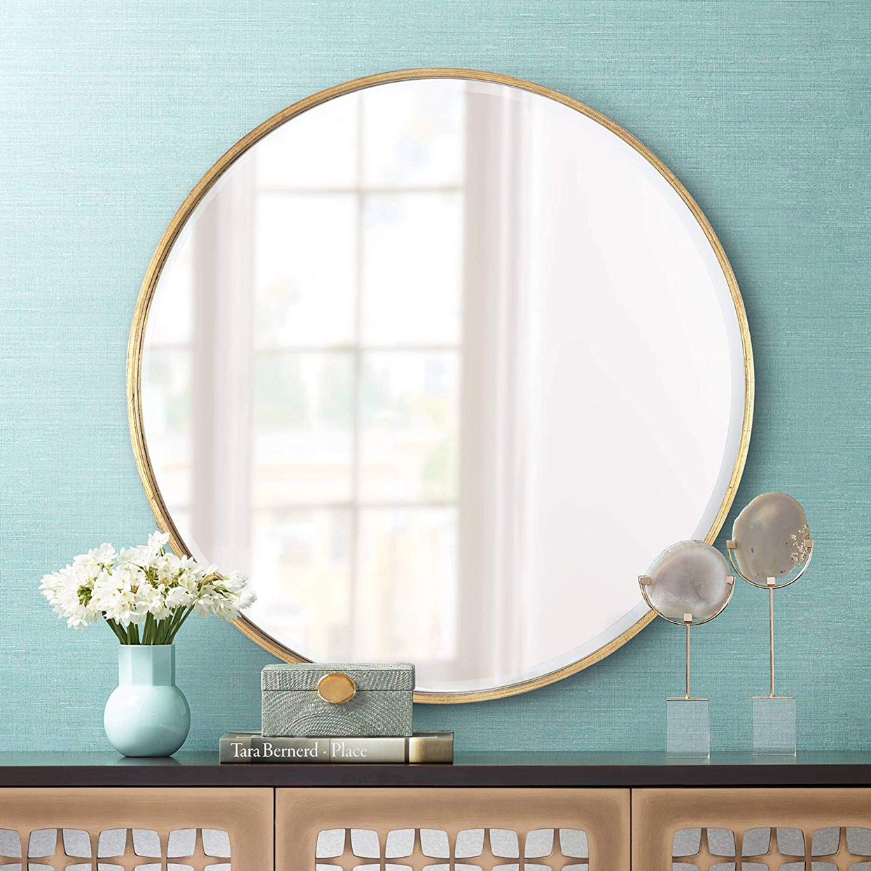 round gold mirror against light blue wall above console table