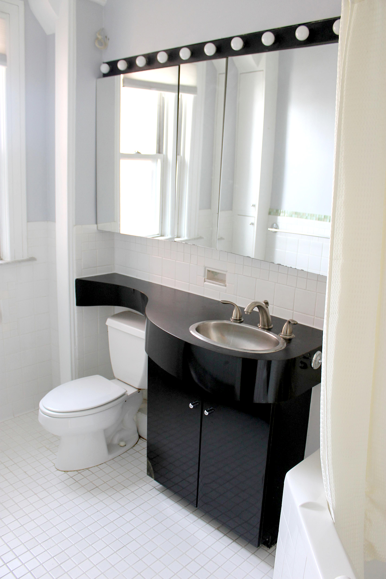 Bathroom with white tile floor and black sink