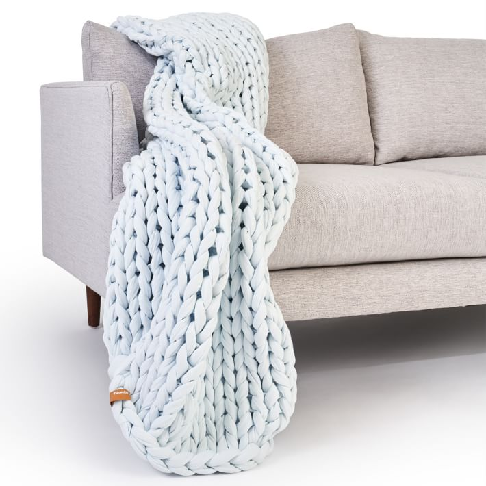 blue chunky knitted blanket on gray couch
