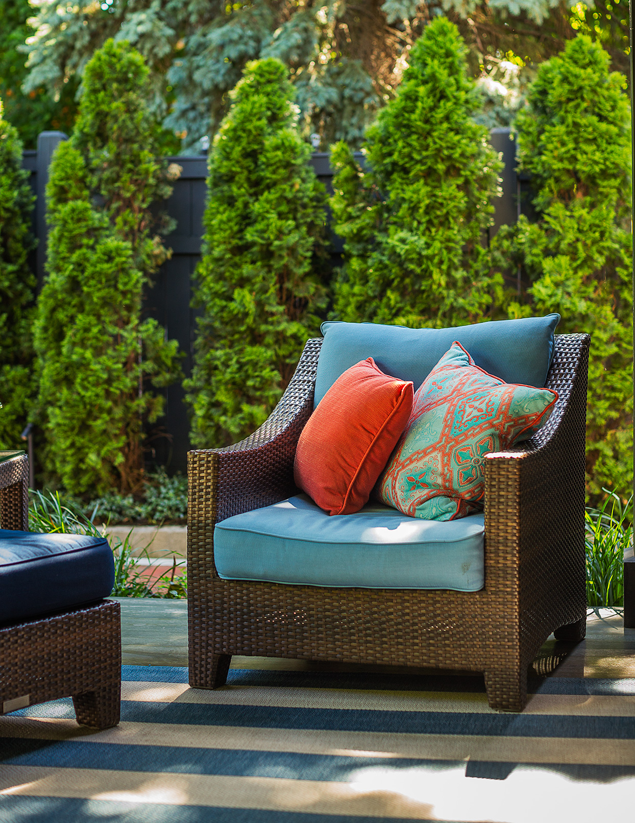 chair on patio with blue cushions and pillows