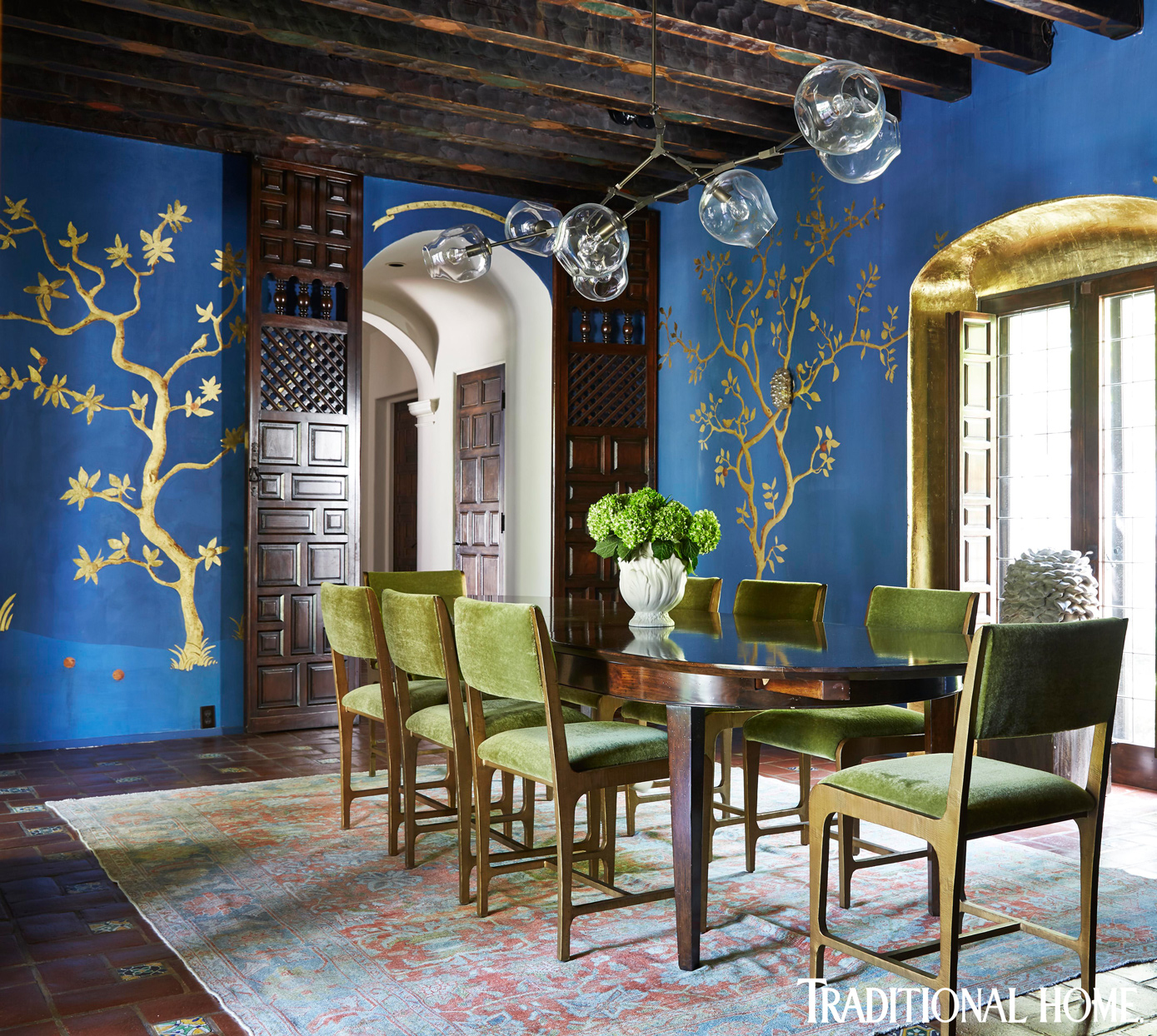 vibrant blue dining room with green chairs and wooden table in spanish colonial home