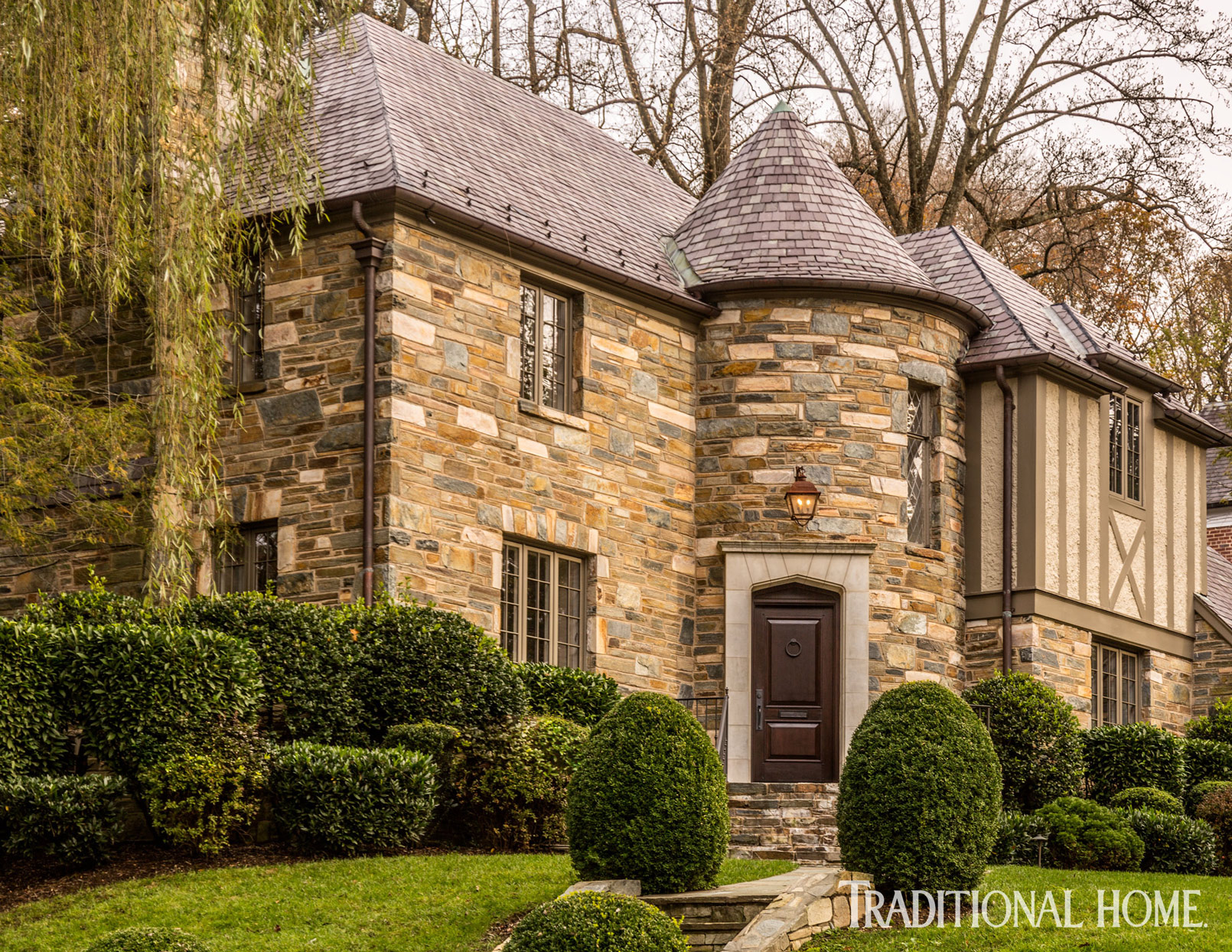 stone tudor home exterior with trimmed hedges