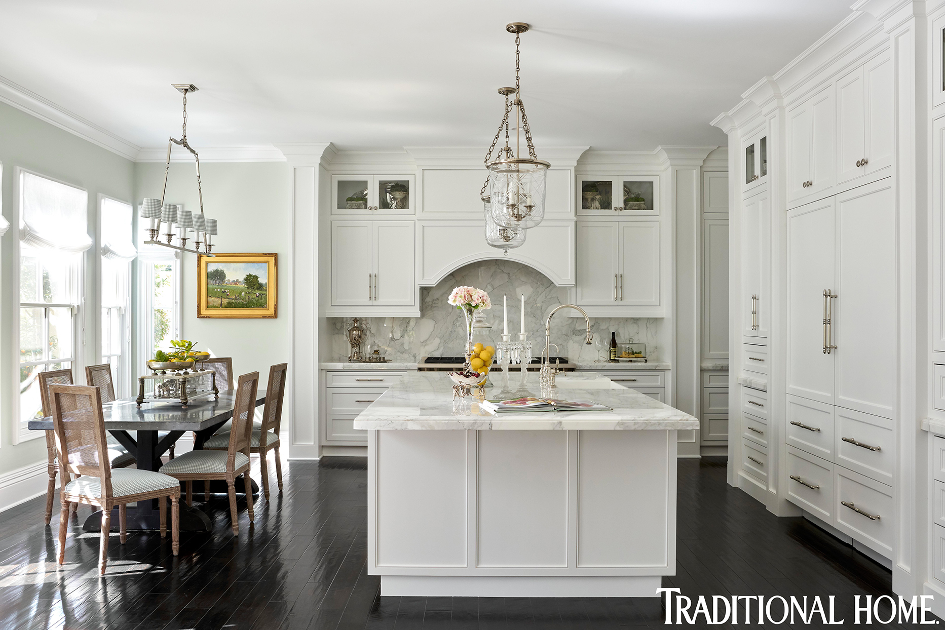 white kitchen with hanging lights and dark wood floors