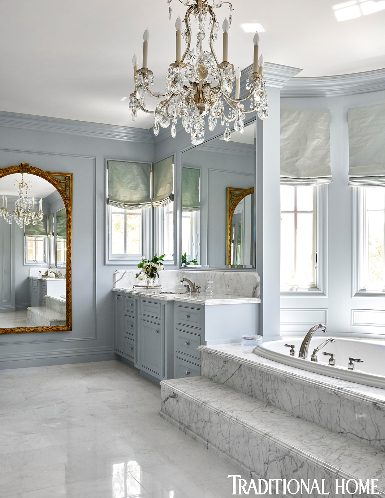 pastel blue and marble master bathroom with chandelier