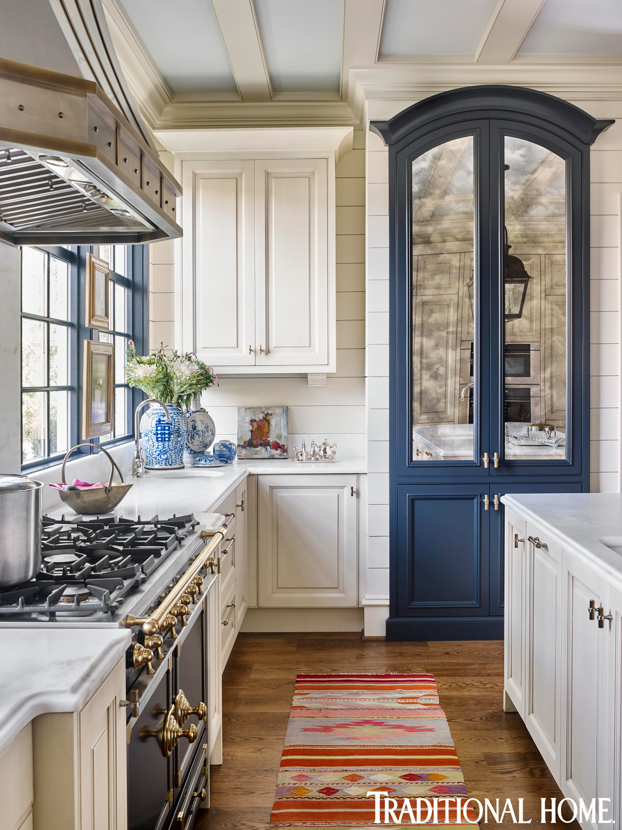 white and blue kitchen with wood floor and red accent rug
