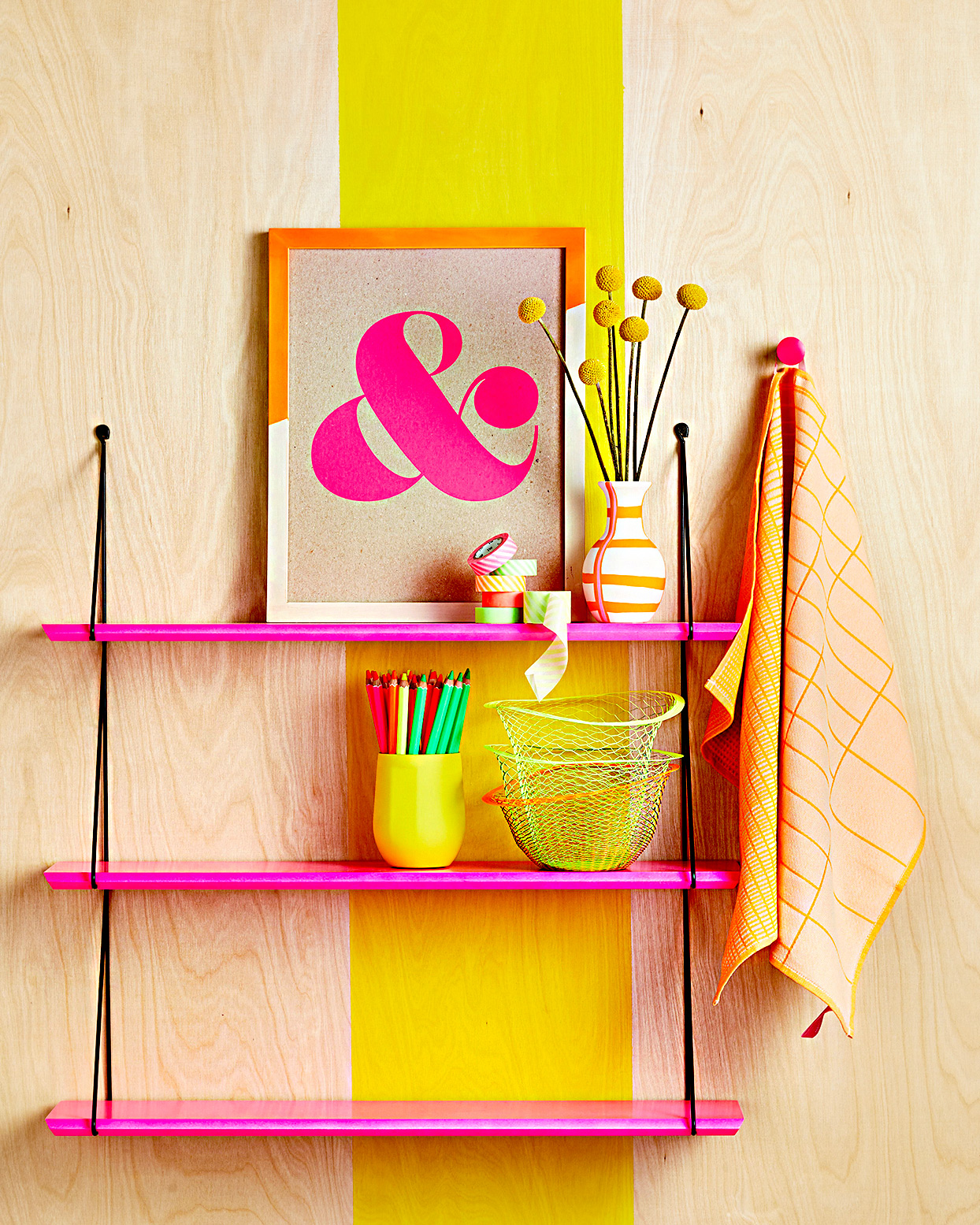 Pink shelving and neon supplies against wooden wall
