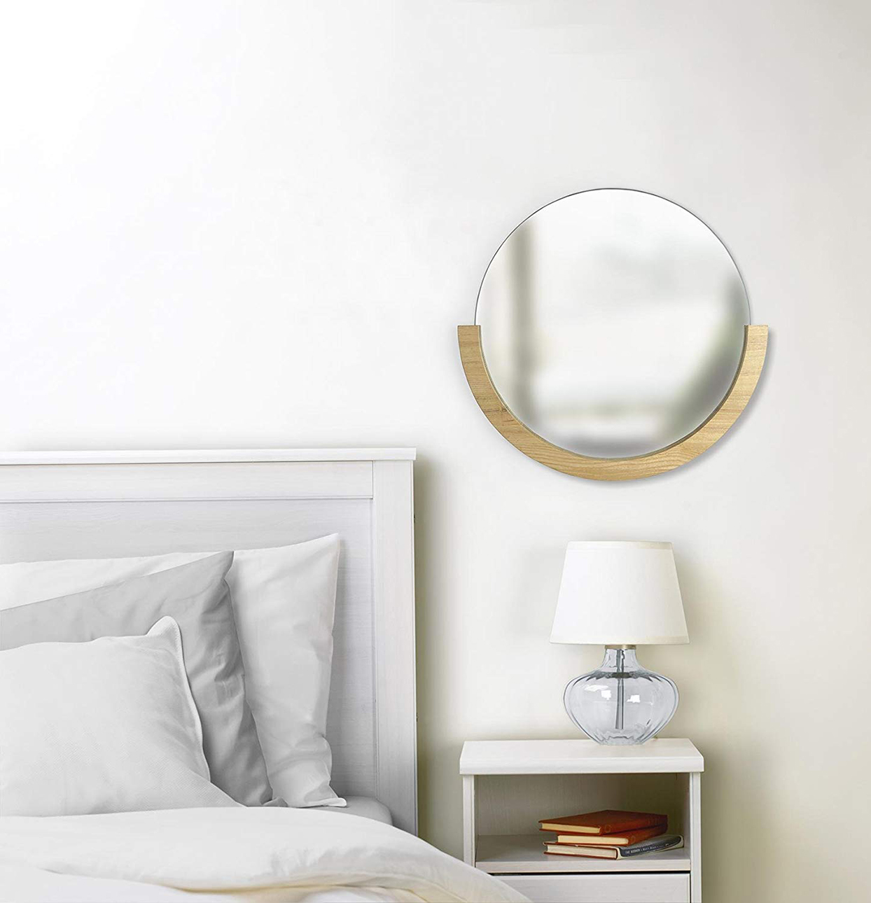 round wood mirror above nightstand next to bed