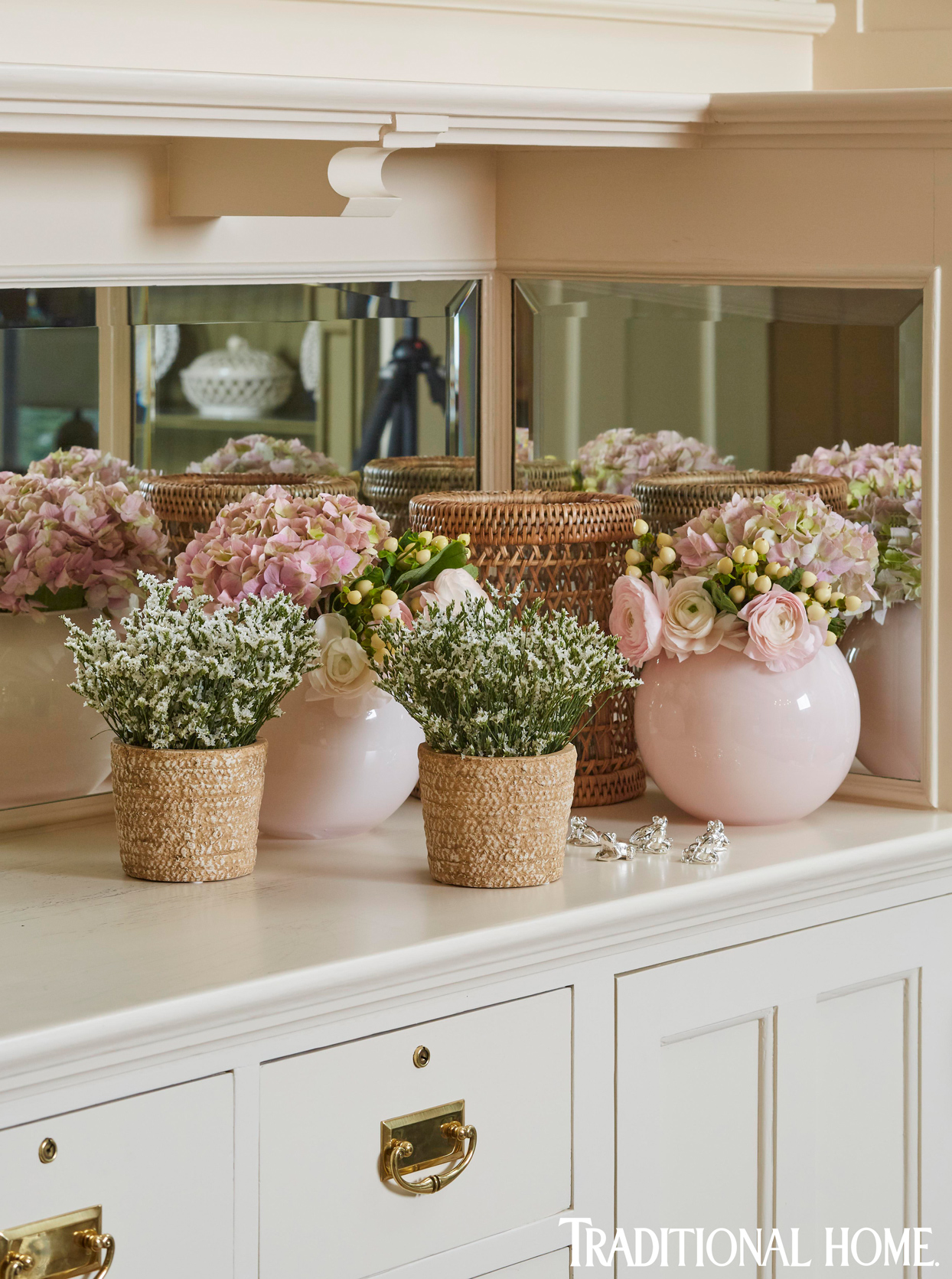 hydrangeas, ranunculus, and stock in wicker and glass containers