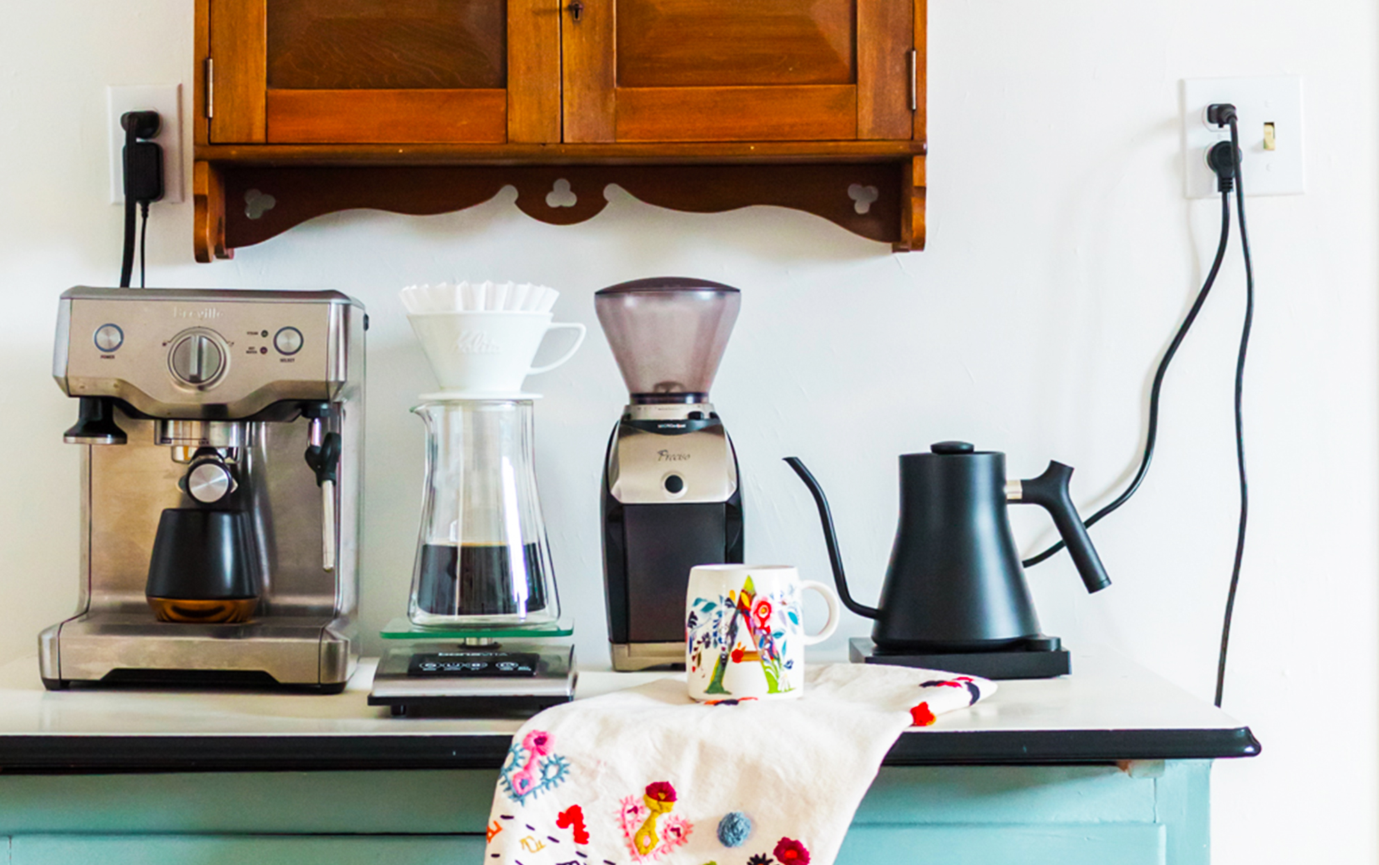 Kitchen counter with coffee makers and power cords plugged in