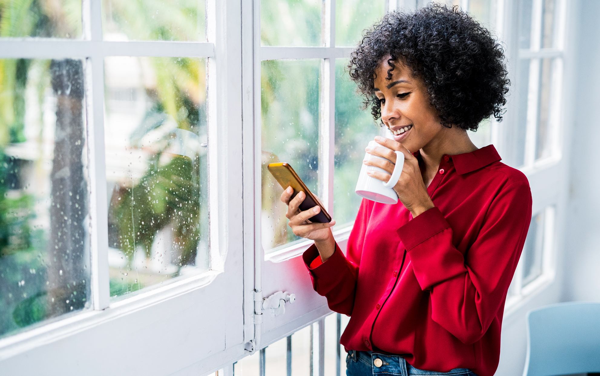 Ethnic woman standing near a window drinking from a mug and looking at a cell phone