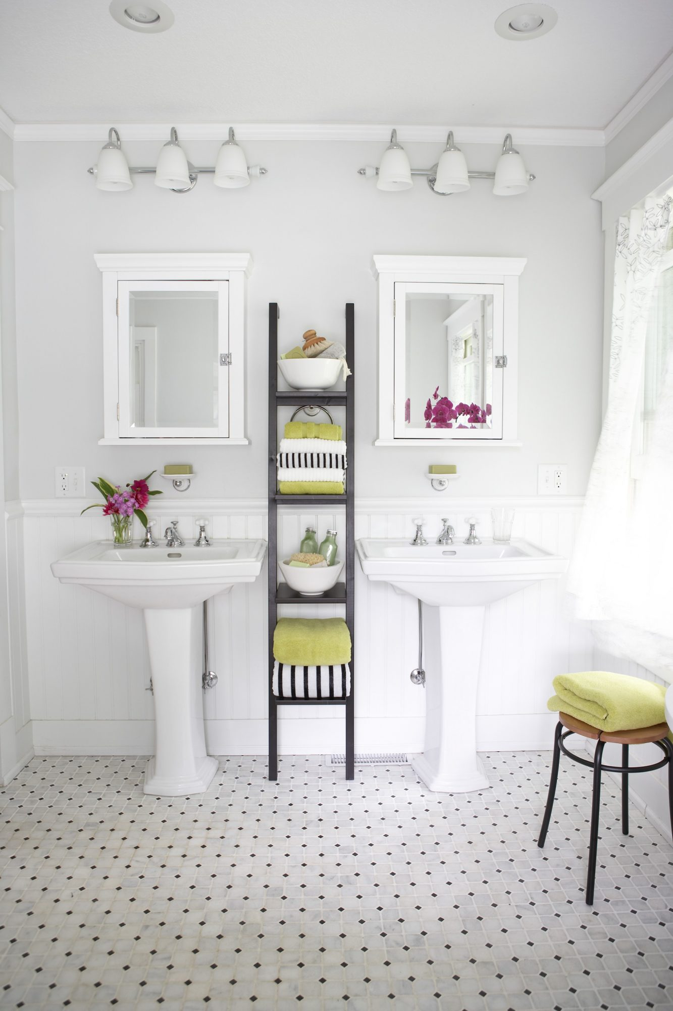 bathroom narrow dark shelves holding towels between dual pedestal sinks