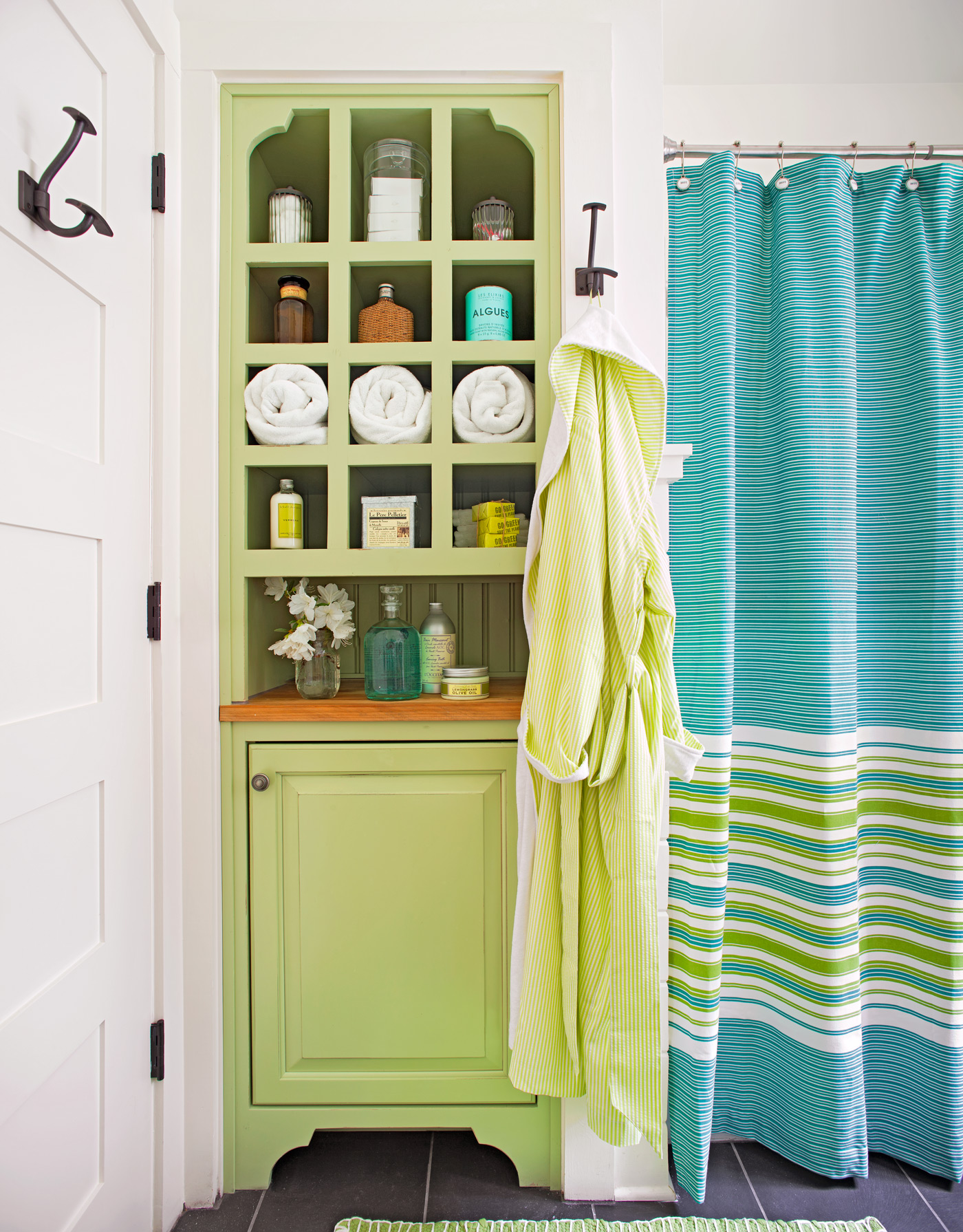 built-in bathroom cabinet with cubbies holding rolled towels