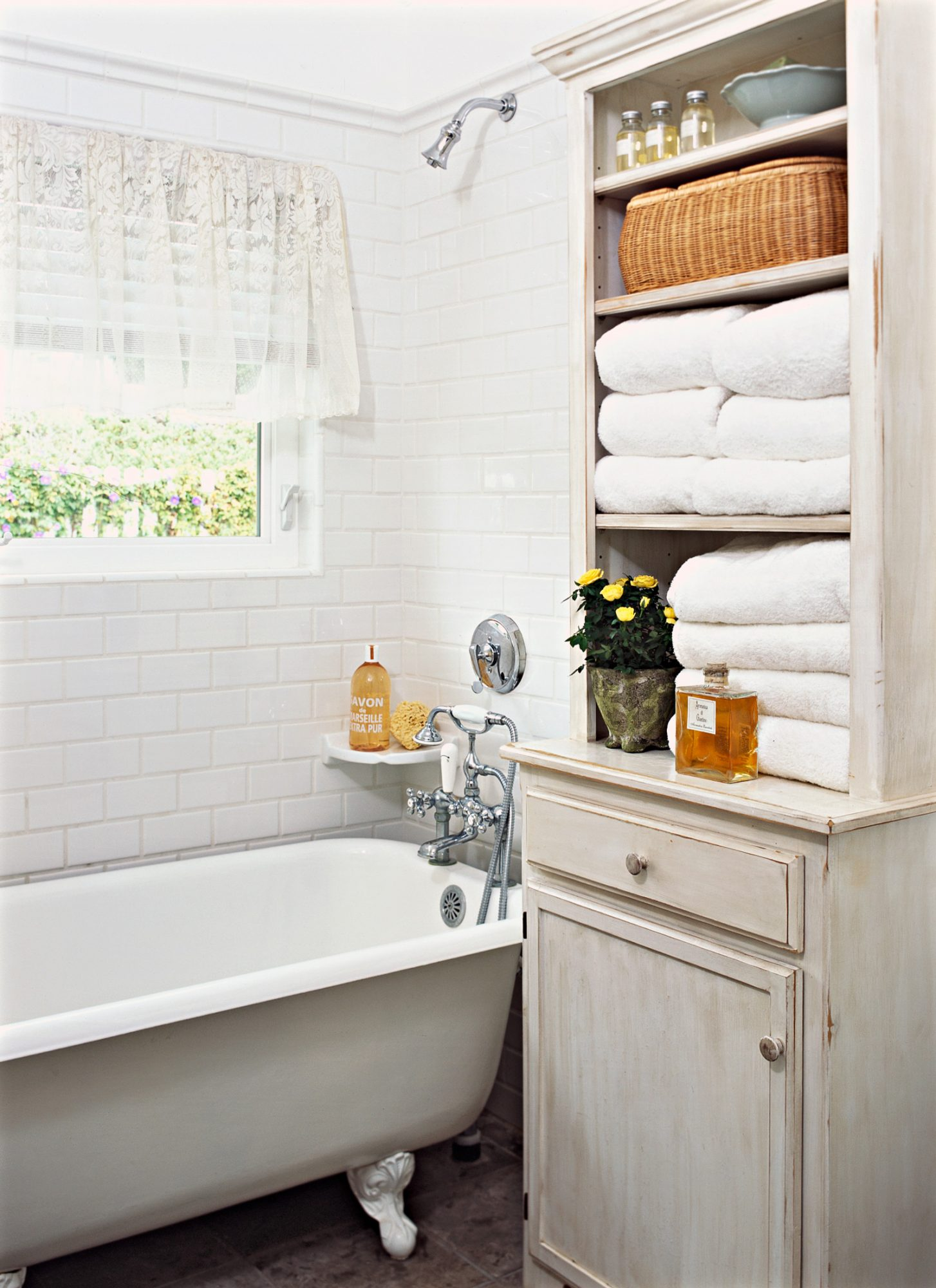 white claw-foot tub tall cabinet with open shelving on top