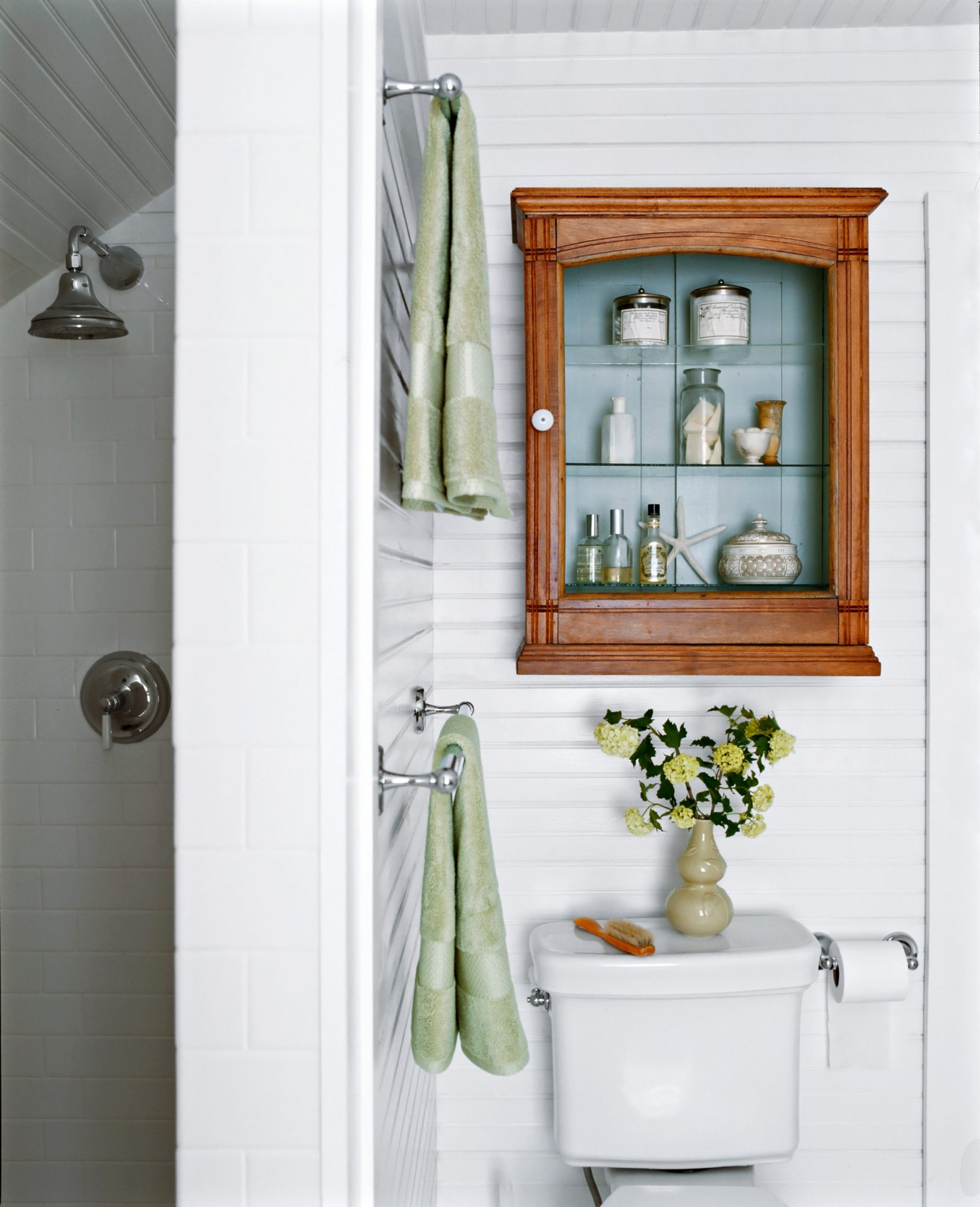close-up white bathroom wooden cabinet with glass shelves