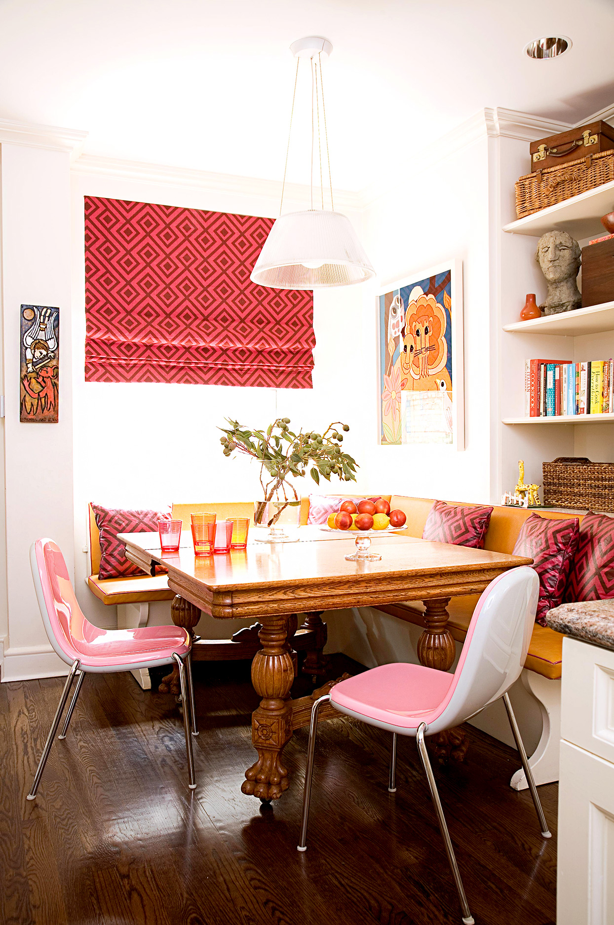 Corner dining area with bookshelf and pink and white chairs