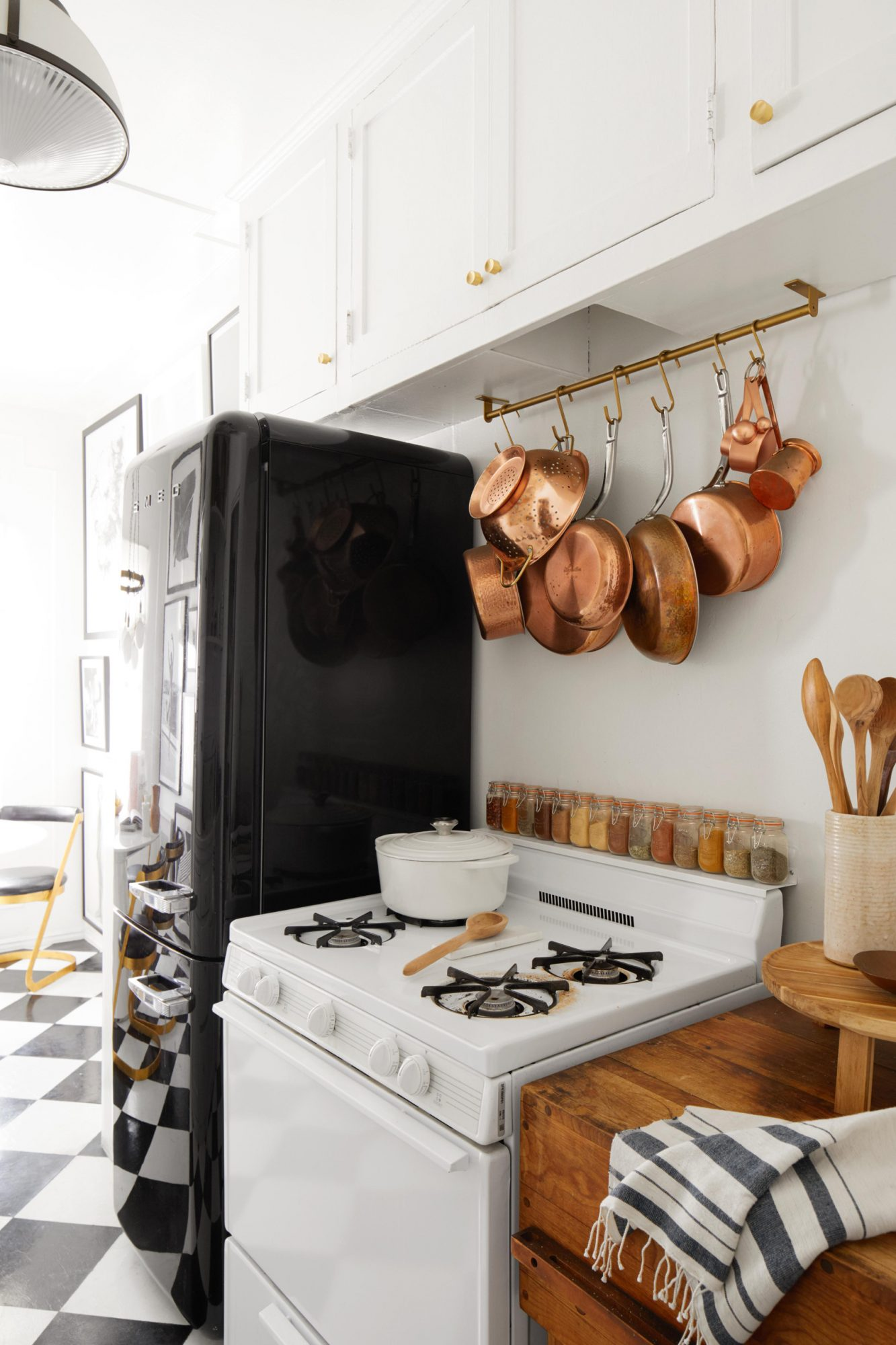 kitchen with white stove black refrigerator and copper dishes hanging