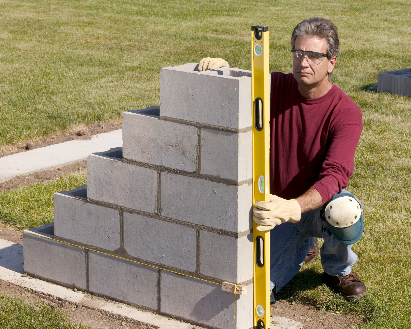 man using level on right side of wall