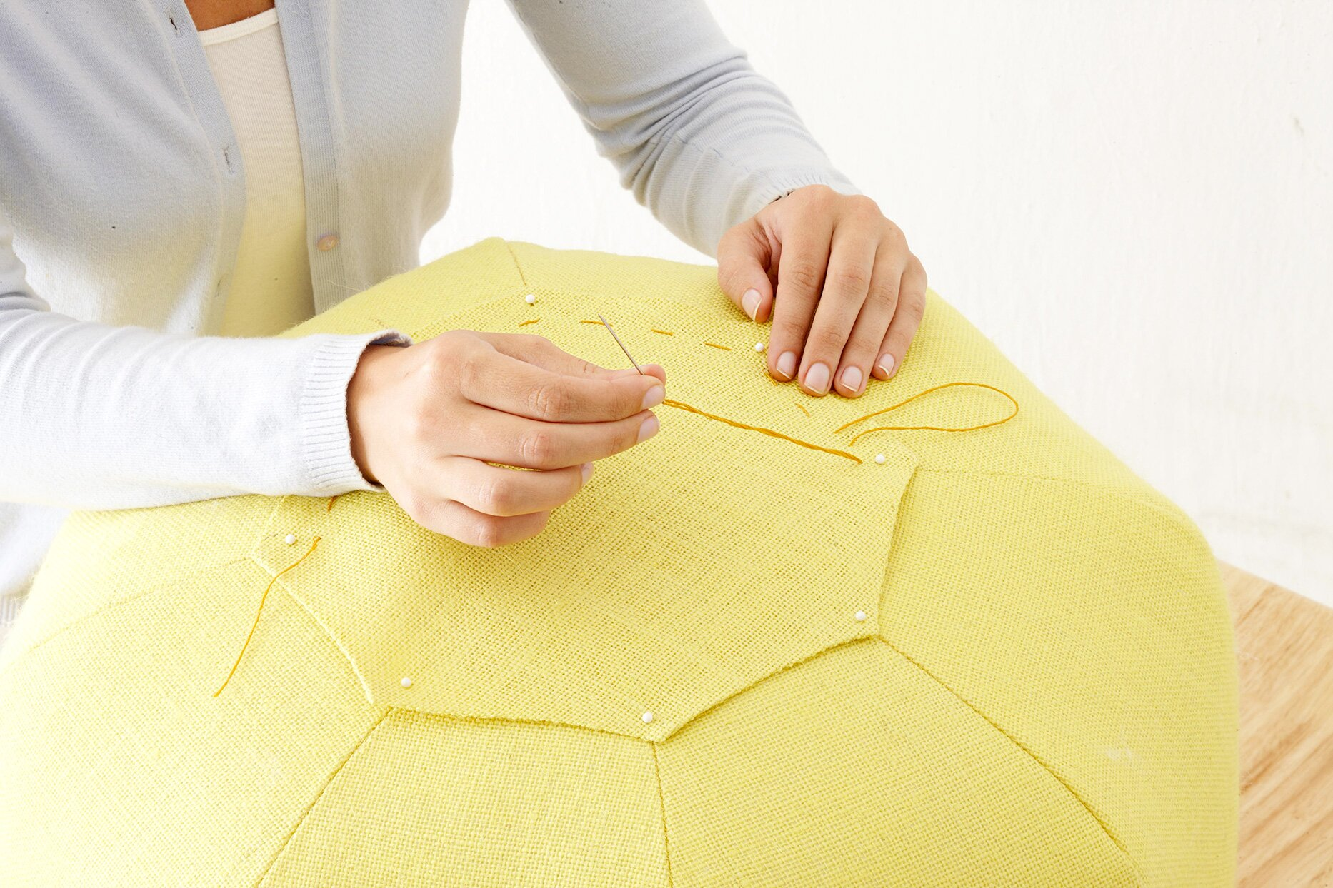 Person pinning octagon fabric onto pouf