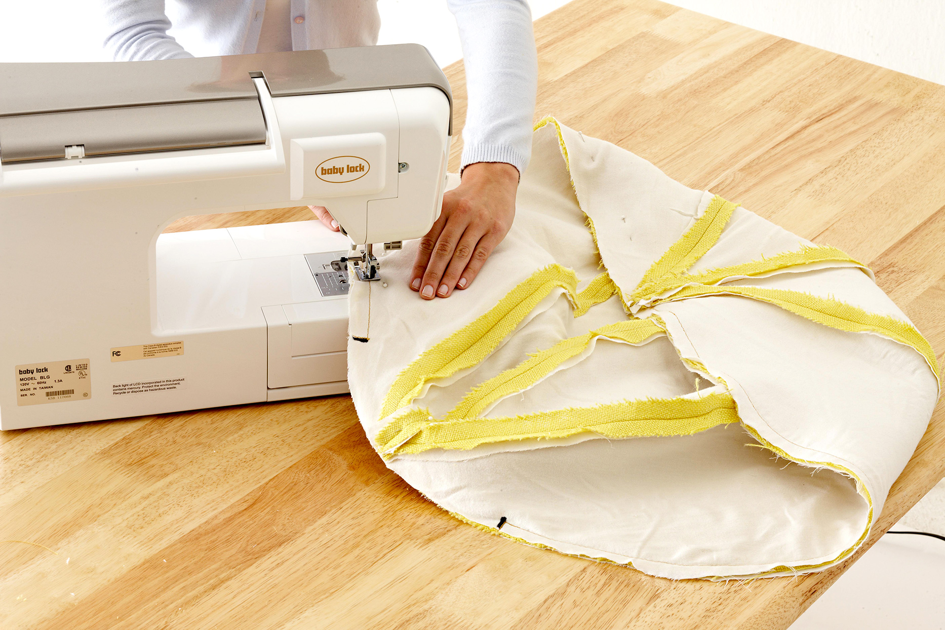 Person using sewing machine to sew pouf together