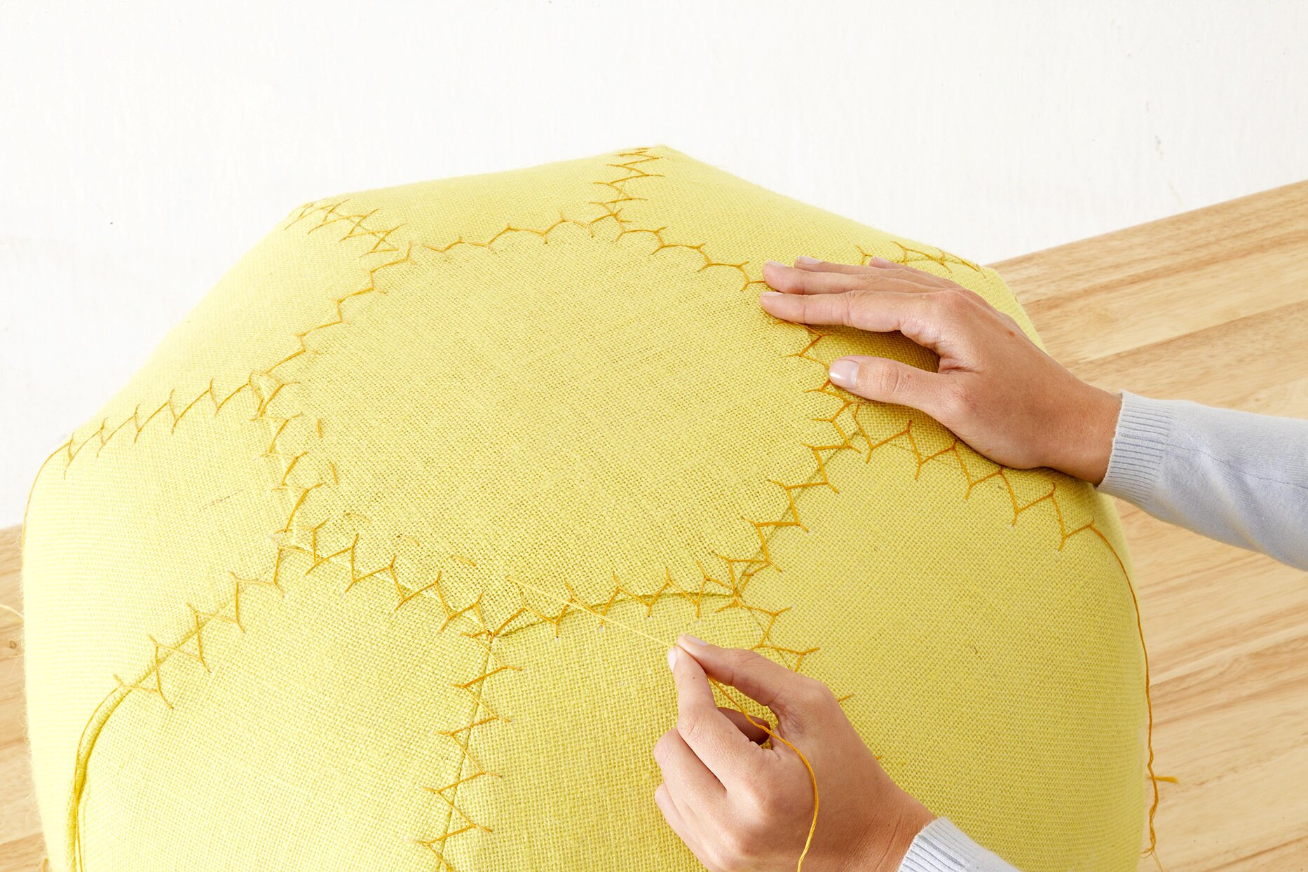 Person sewing octagon on pouf