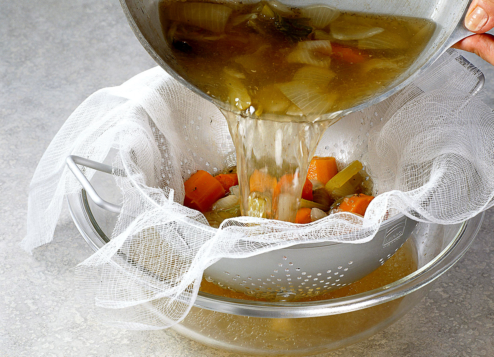 Straining broth through cheesecloth in colander
