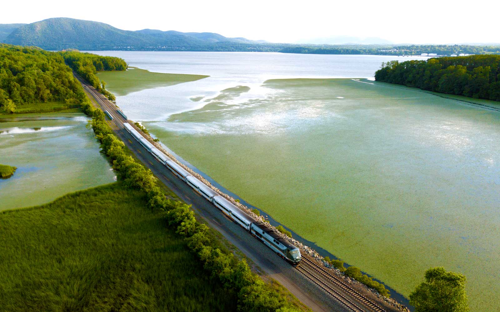 train riding past body of water