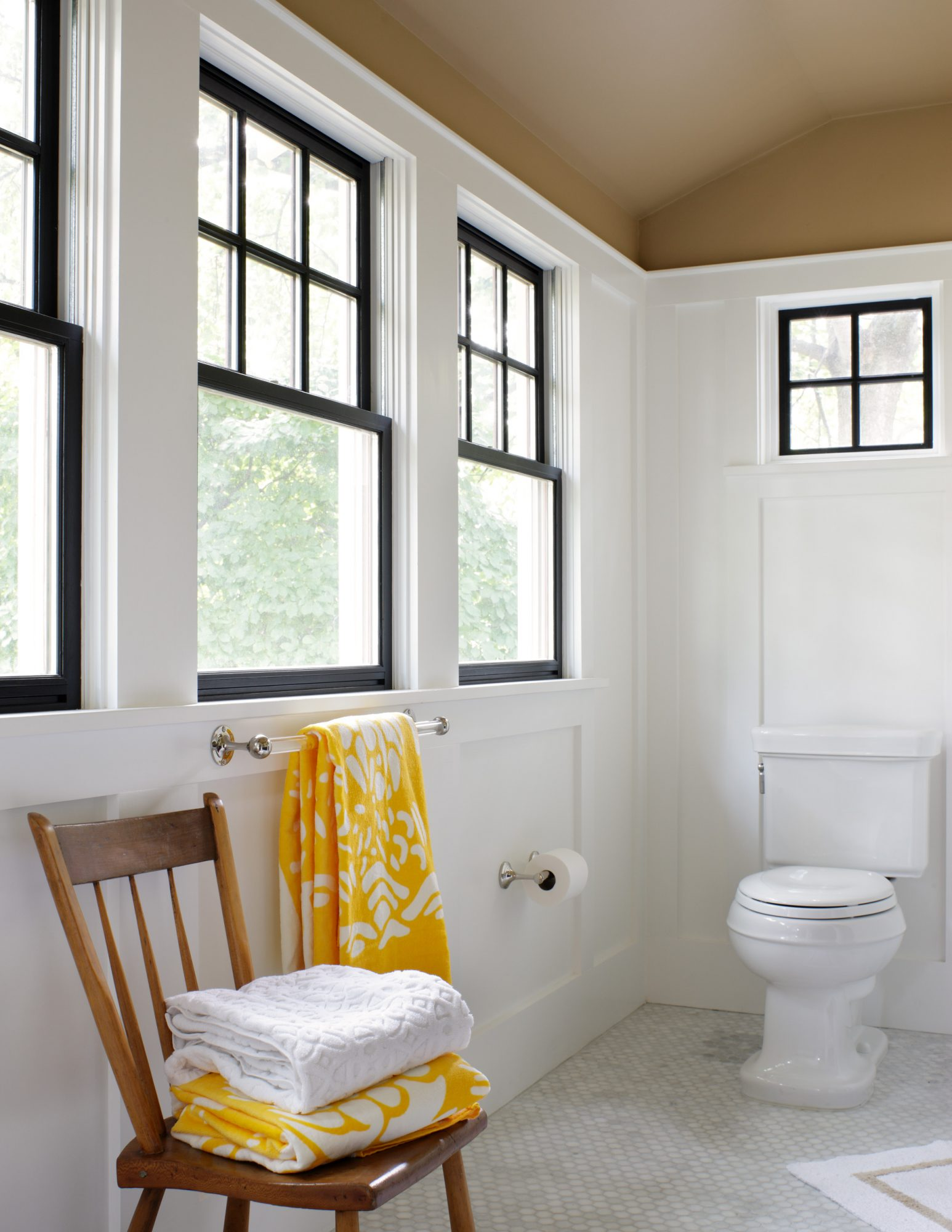 white bathroom black trim windows with chair holding towels