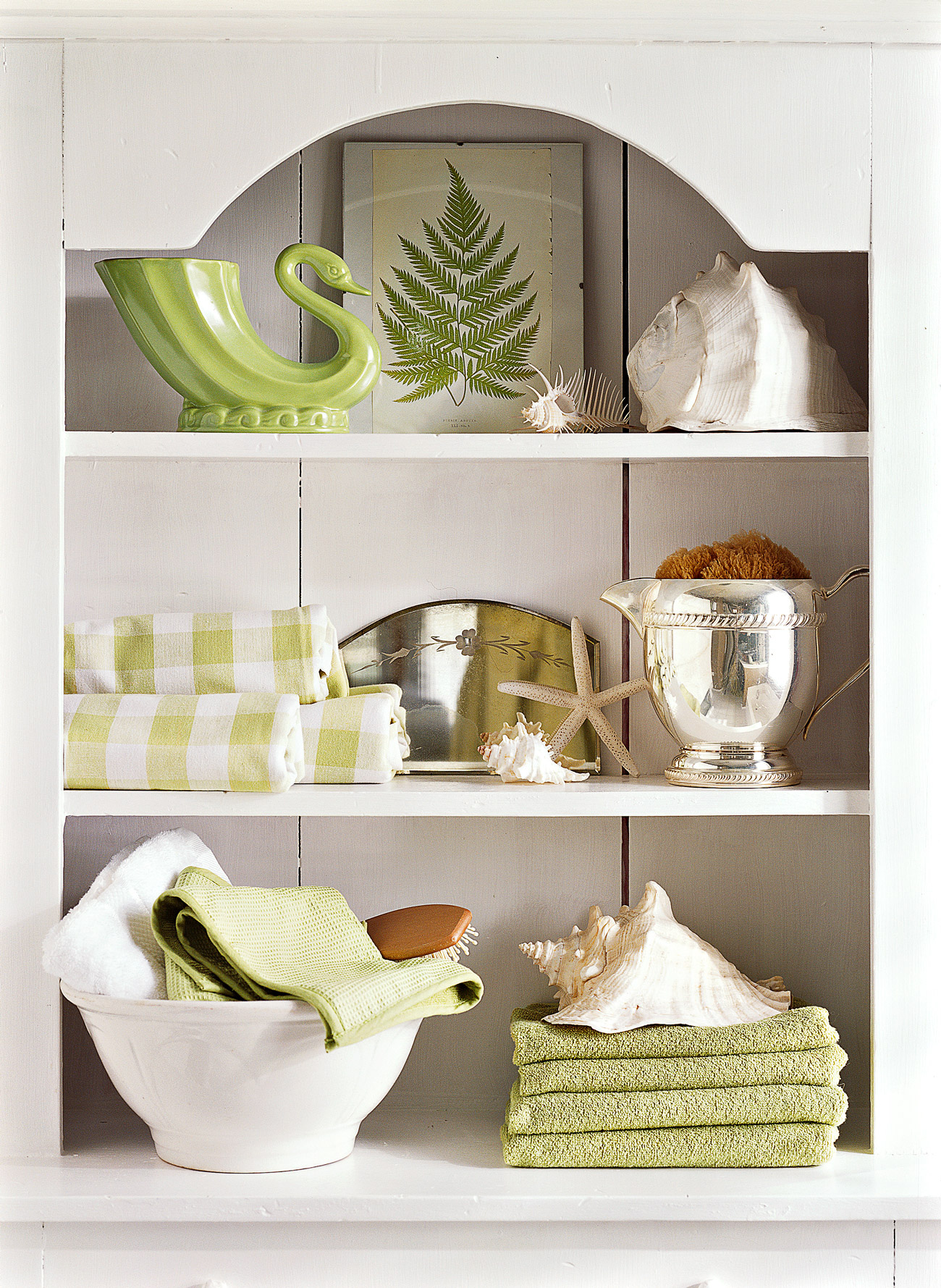 white hutch in bathroom with towels and other items