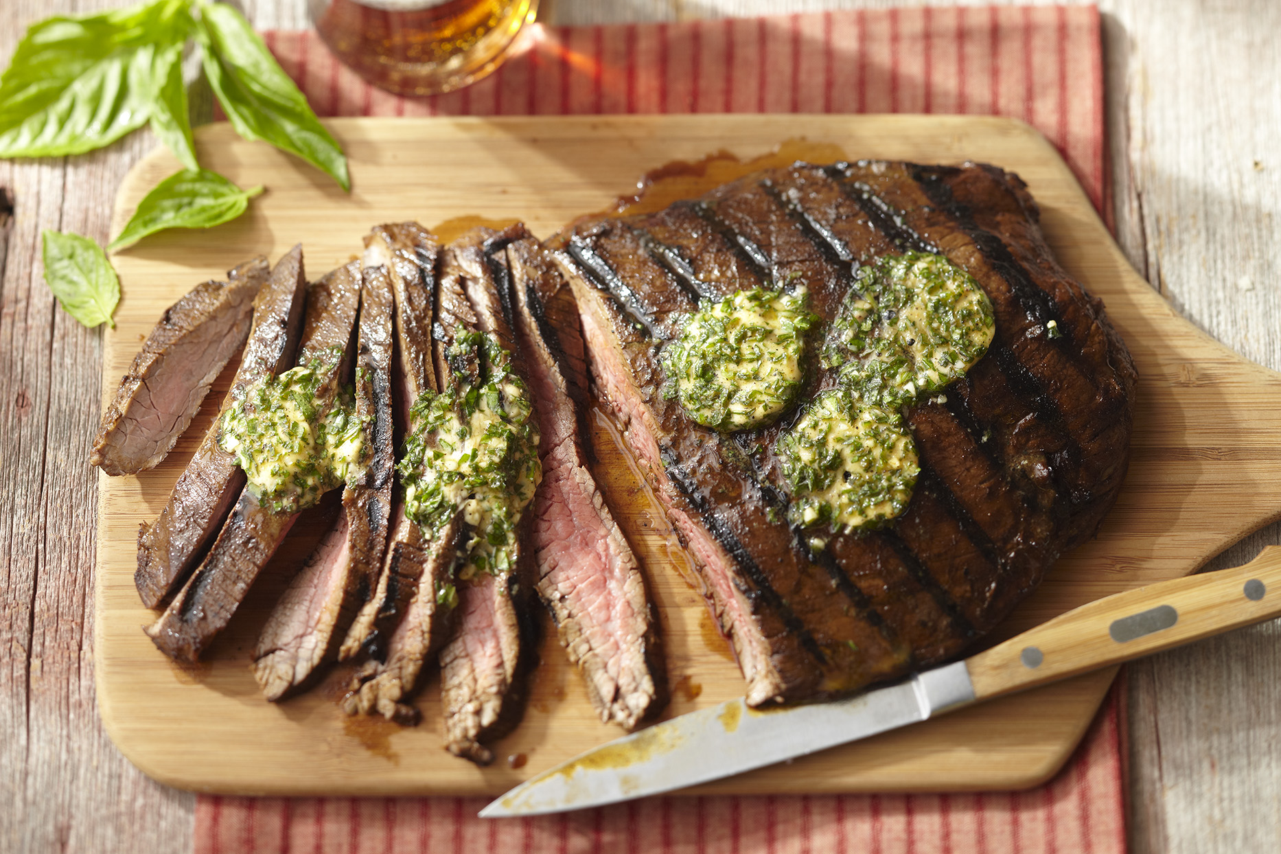 Flank steak on a wooden cutting board. Half the steak is sliced into strips with knife resting next to the steak on the cutting board. Pats of herb butter are melting over the top of the meat.