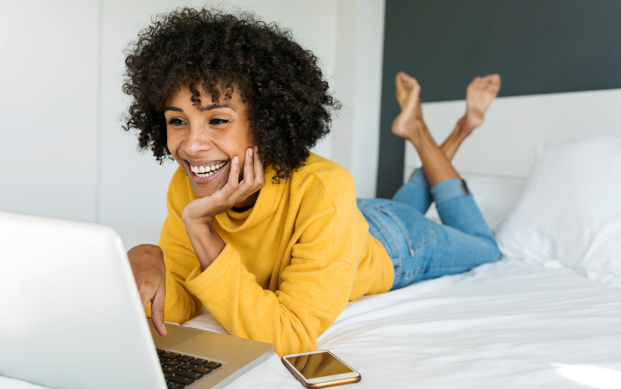 African American woman with a laptop laying on her bed