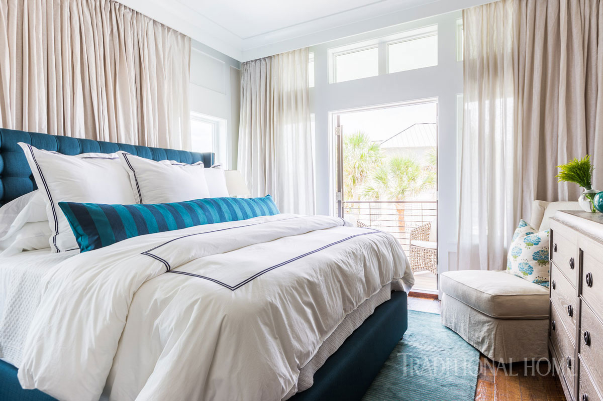 guest bedroom with blue pillow and tufted headboard