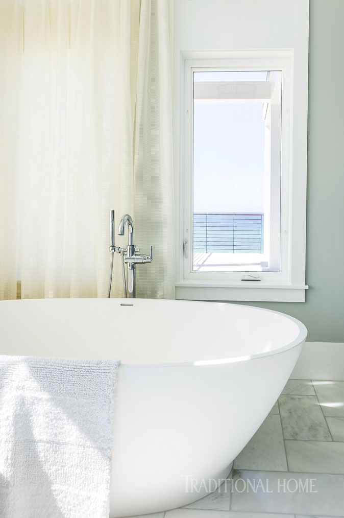 master bath with freestanding tub and green walls