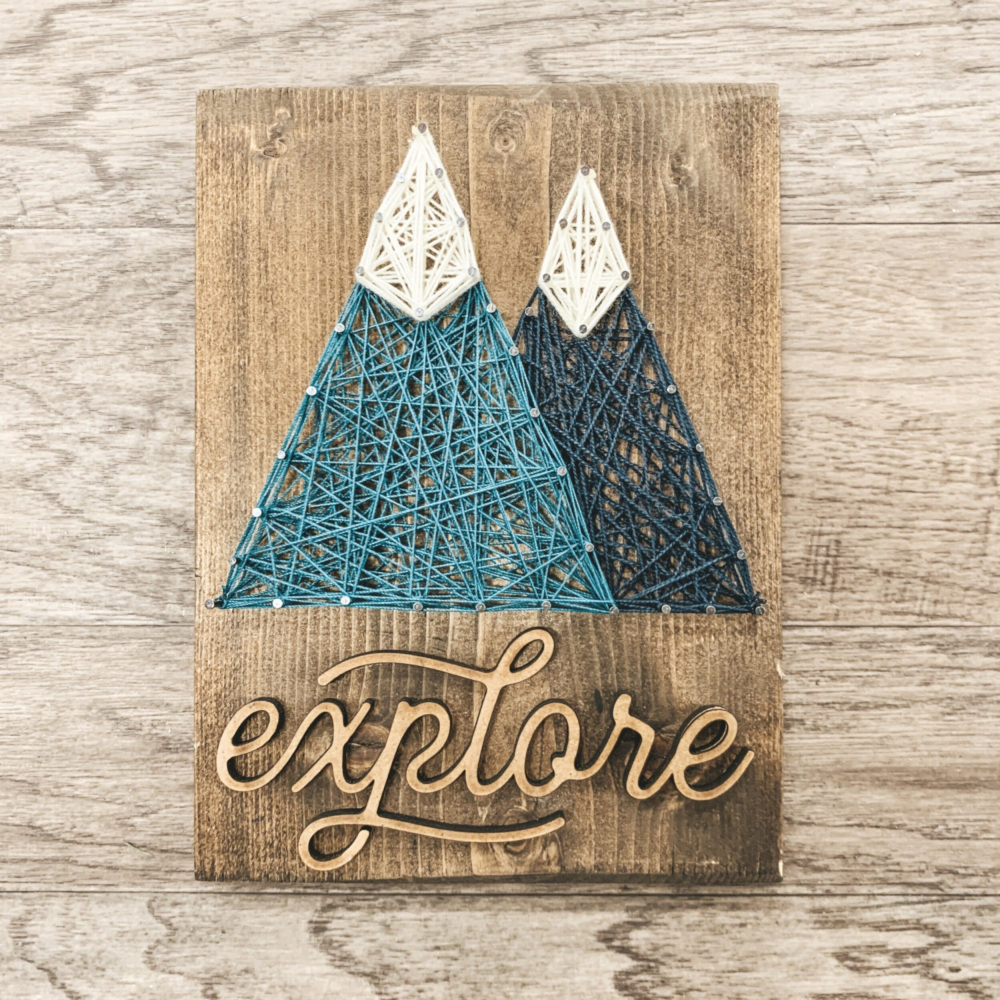 wood board with nails and string in a mountain pattern