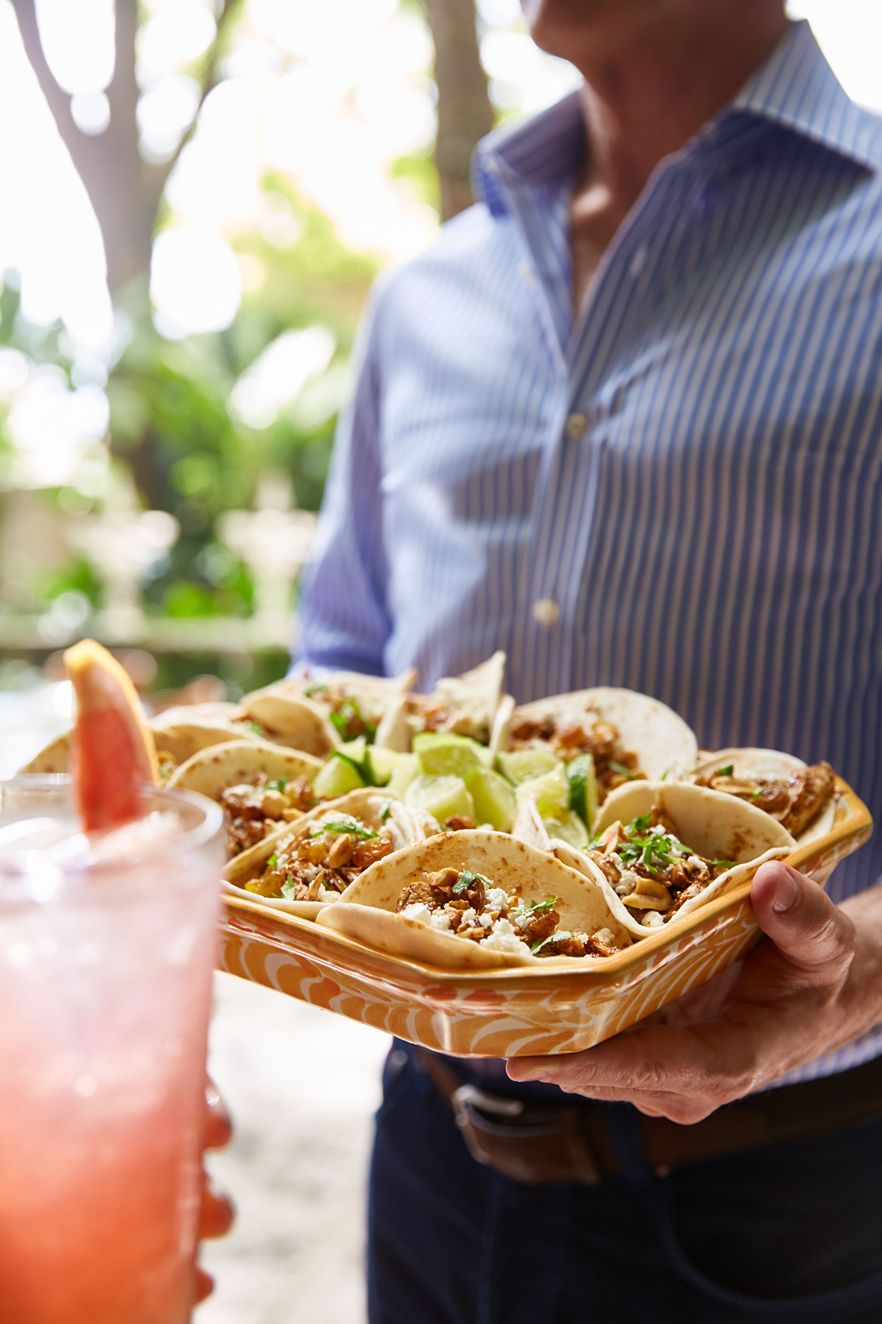 Person holding tray of tacos